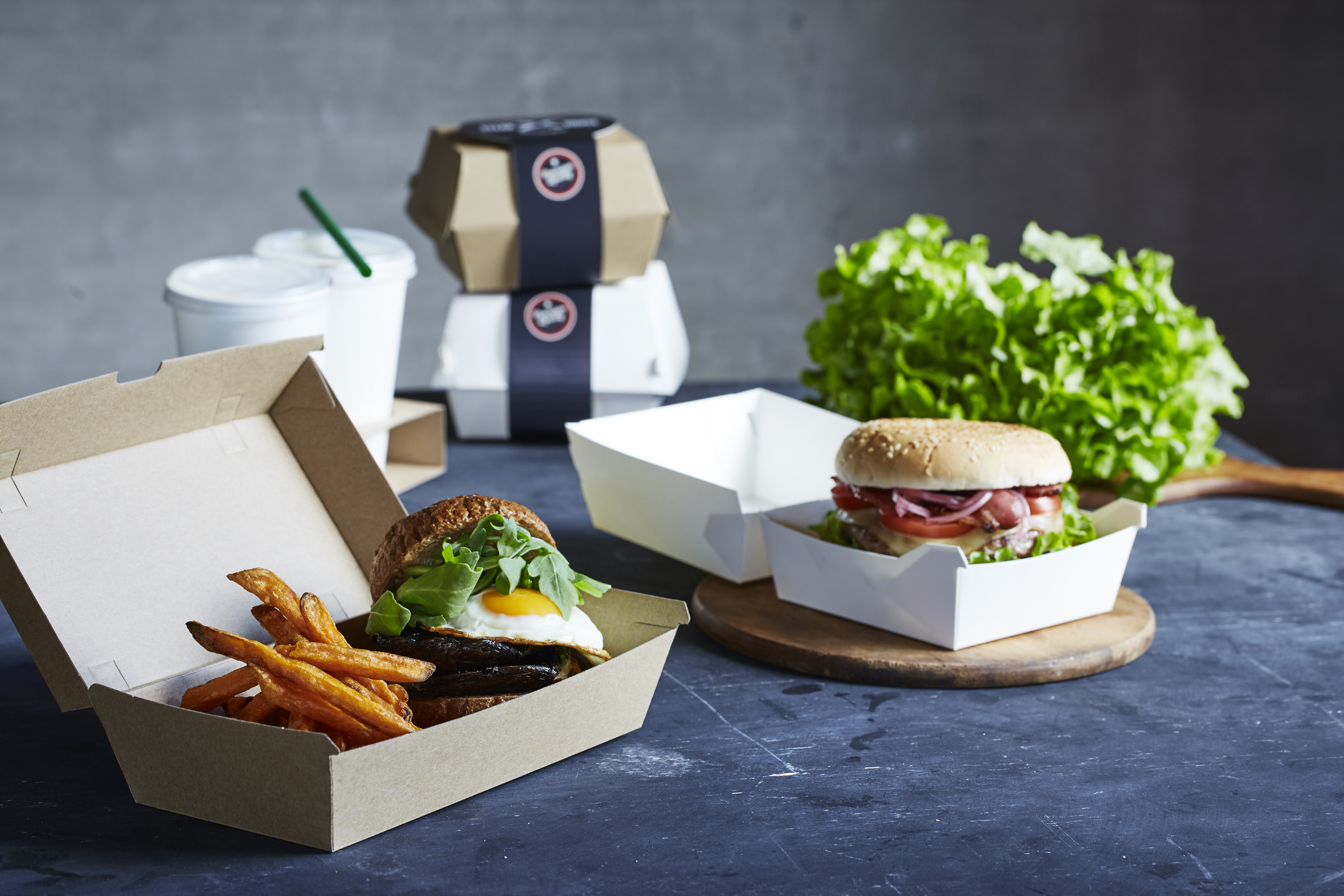 Burgers packaged in cartons for food delivery.