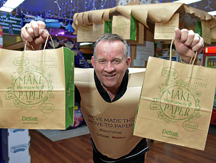 Image of Bruce Lutcherhead smiling and holding paper bags. He is also wearing an outfit made out of a large paper bag.