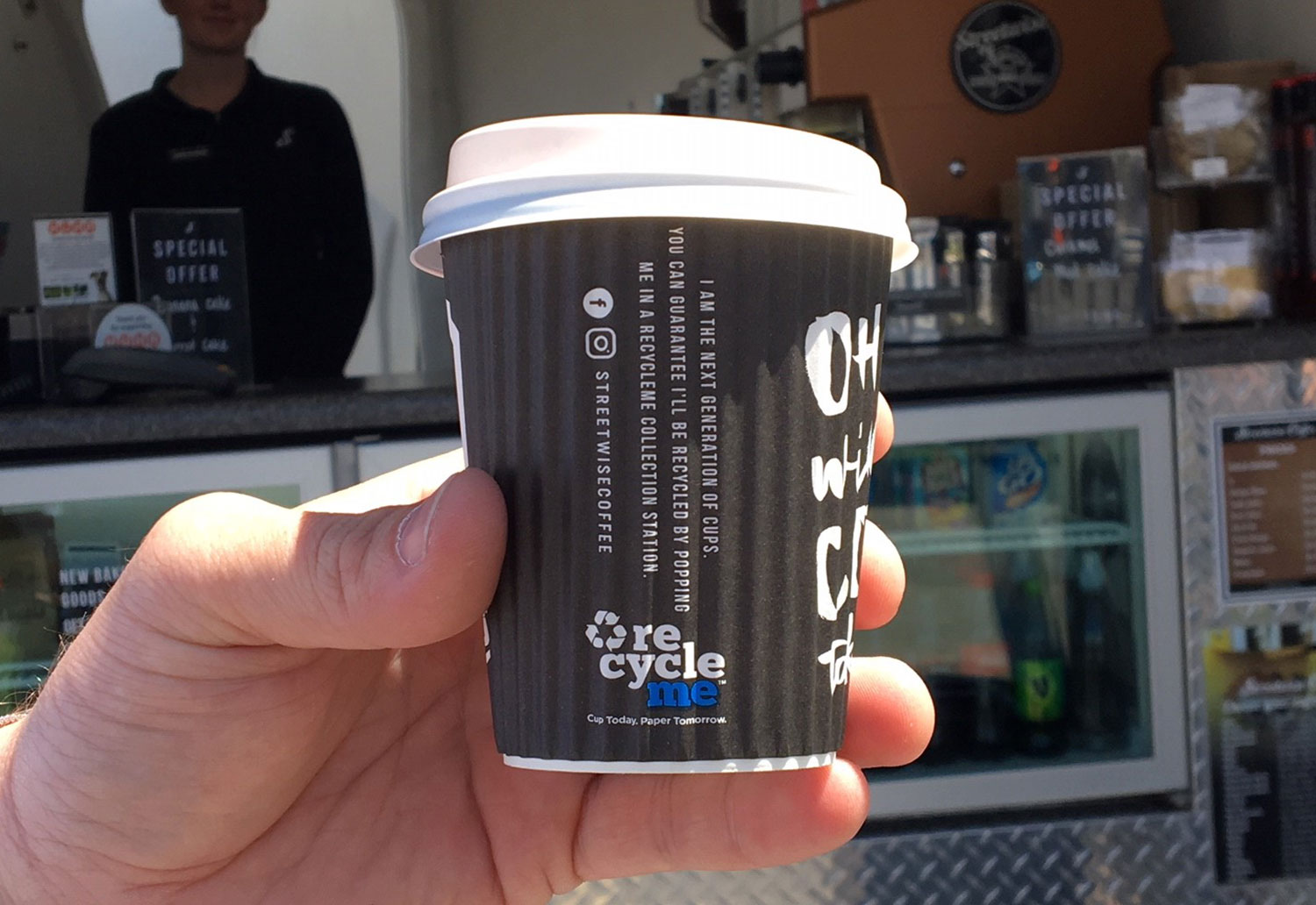 Image of Streetwise Coffee Cup held in front of a Streetwise Coffee Cart