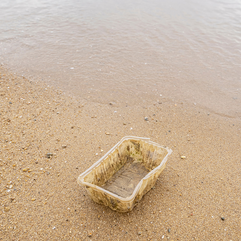 Image of plastic container sitting in sand
