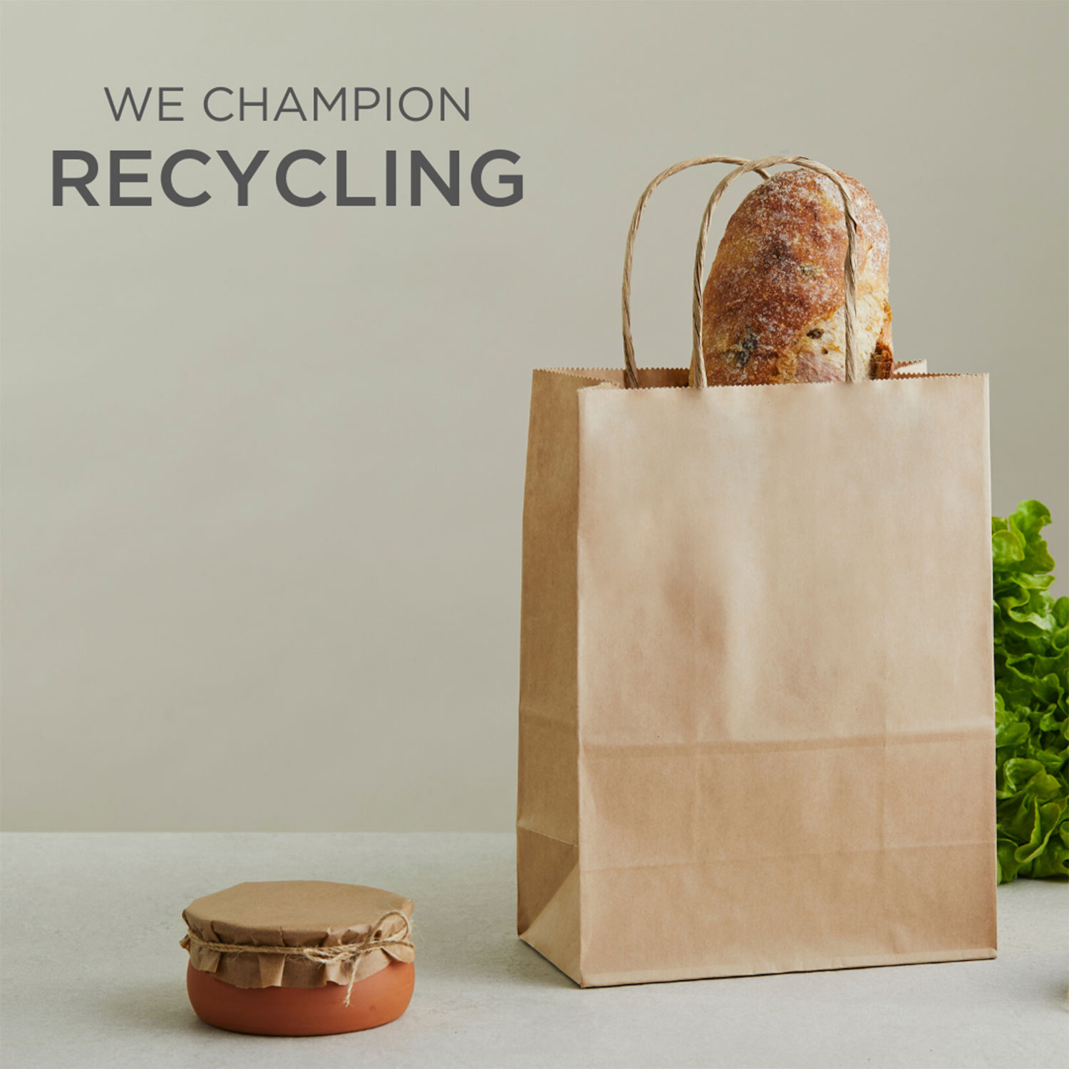 Image of a recyclable paper bag with words 'we champion recycling'